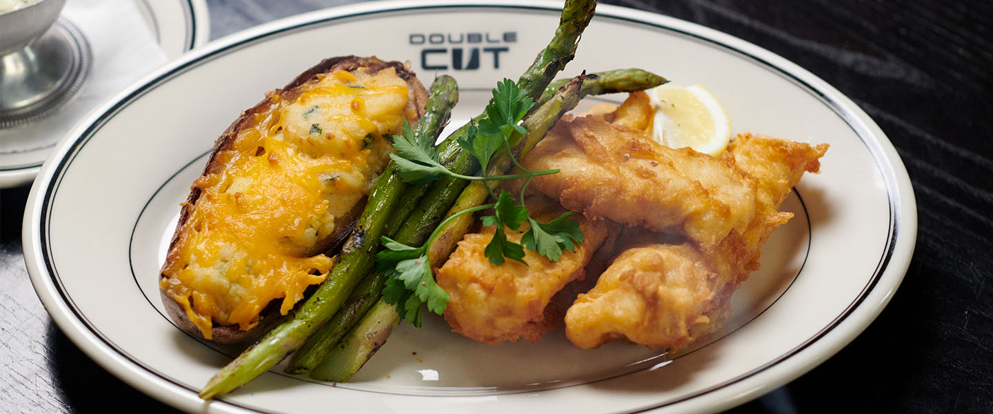 a plated fish fry, with twice baked potato, asparagus and fried haddock