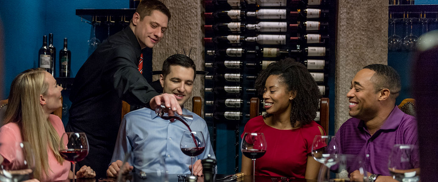 a server pouring wine for a group of four