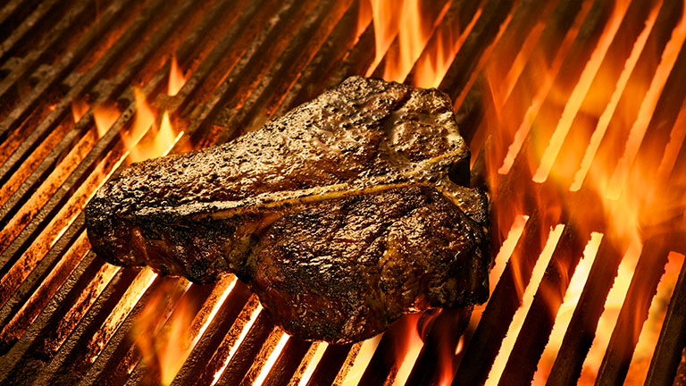 T-bone steak grilling over charcoal and flames