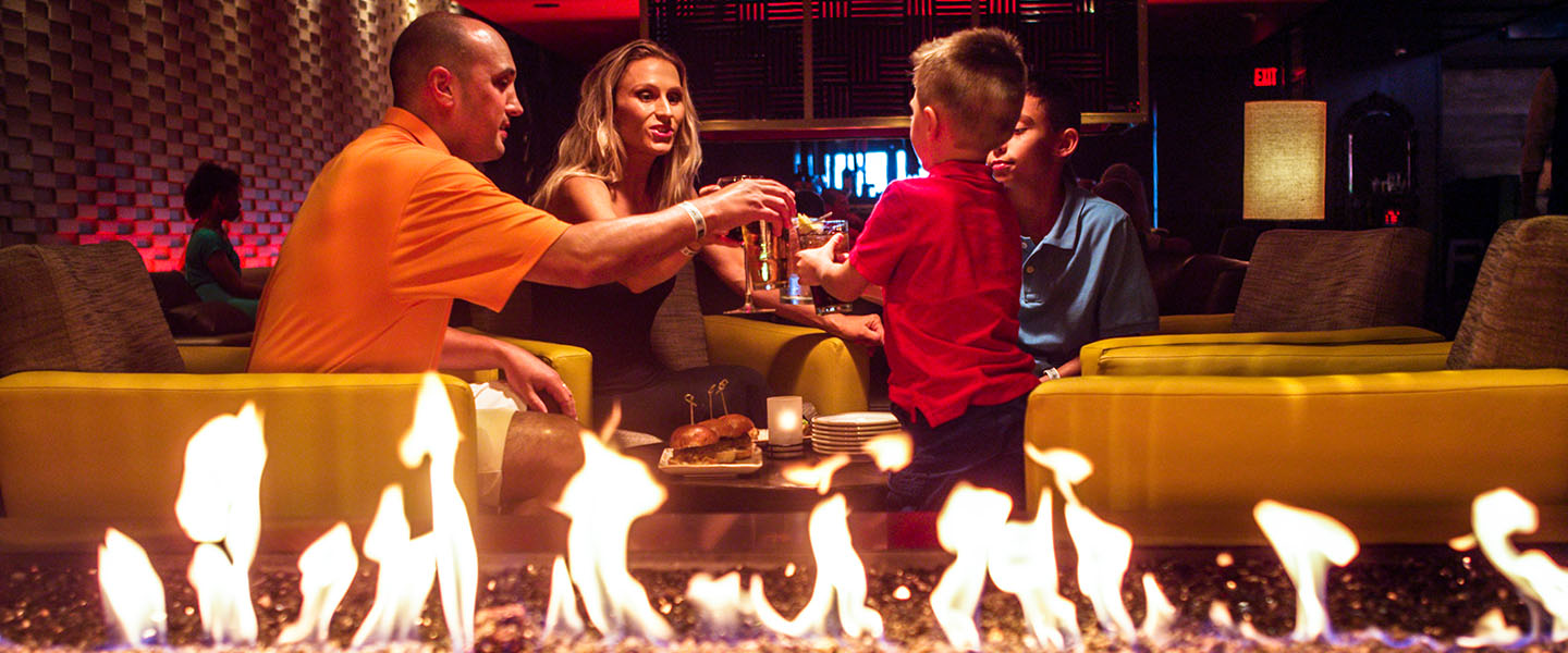 a family of four doing cheers with their drinks, flames from the indoor fire pit in the lounge in the foreground